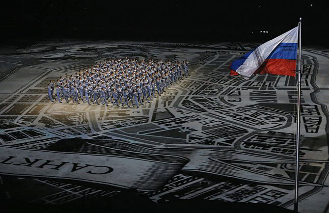 Performers take part next to a Russian national flag during the opening ceremony of the 2014 Sochi Winter Olympic Games